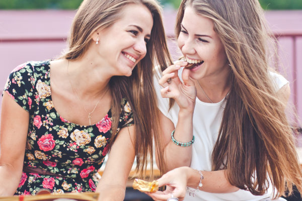 Two young female friends laugh and eat chocolate outdoors