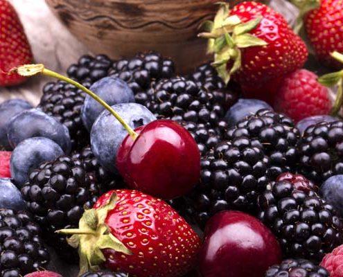 tasty summer fruits on a wooden table. Cherry Blue berries strawberry raspberries Blackberries pomegranate