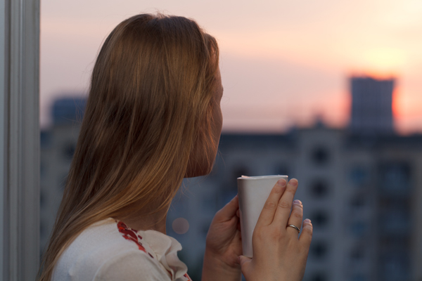 Girl drinking tea in the evening on the balcony.