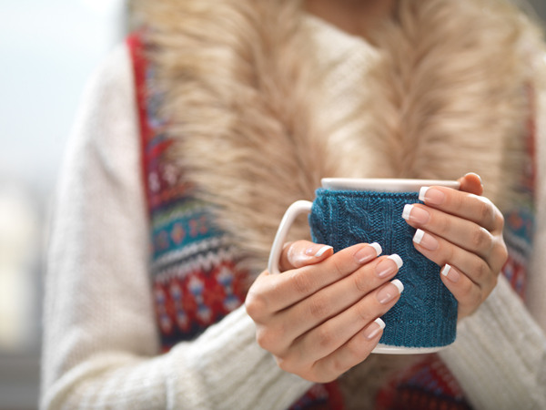 Woman holds a winter cup close up on light background. Woman hands with elegant french manicure nails design holding a cozy knitted mug. Winter and Christmas time concept.