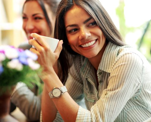 Cheerful businesswoman holding cup of coffee